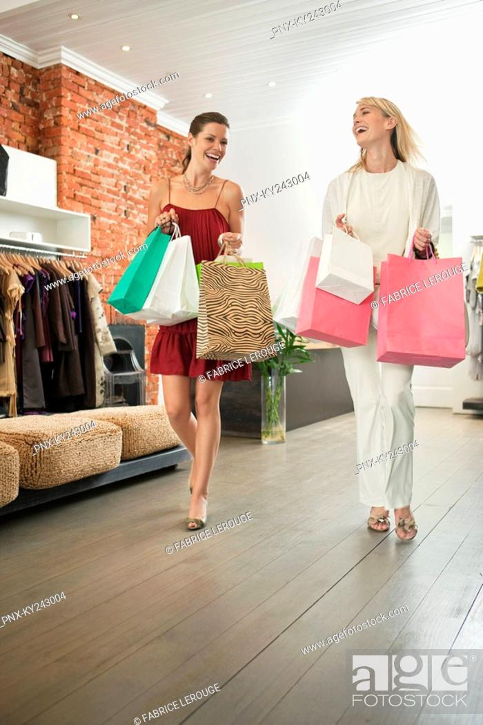 Stock Photo: Two women holding shopping bags in a boutique.