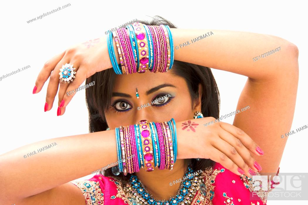 Stock Photo: Beautiful face of a Bengali bride with her arms across her head covered with colorful bracelets, isolated.