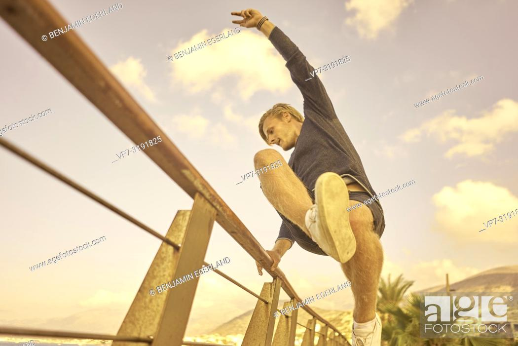 Imagen: Man jumping over handrail, Stalida, Crete, Greece.