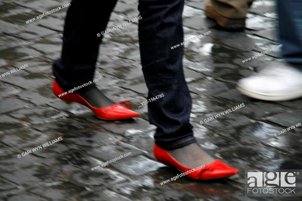Stock Photo: woman wearing red shoes walking in town.