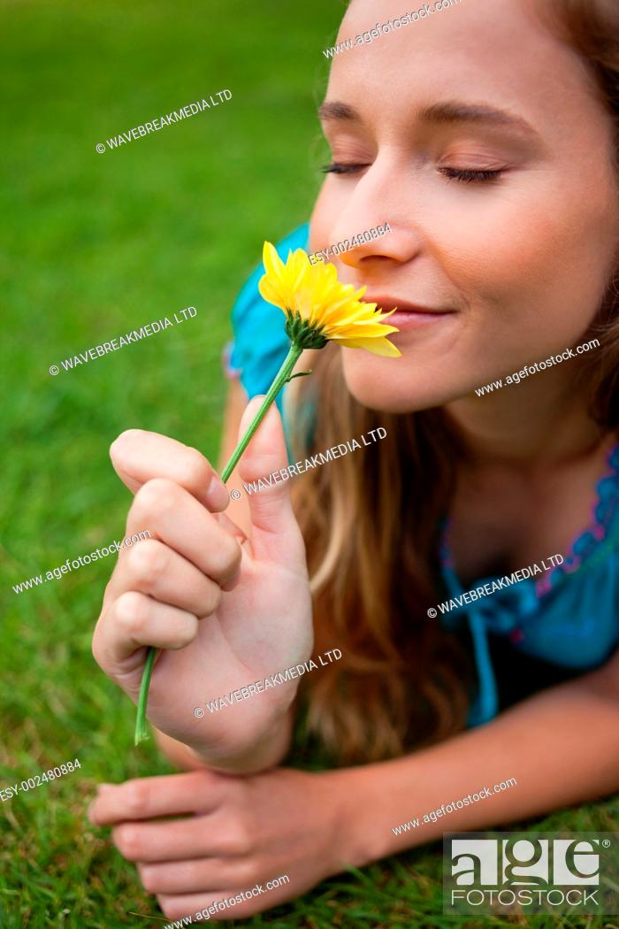 Stock Photo: Young relaxed woman smelling a beautiful yellow flower while lying on the grass.