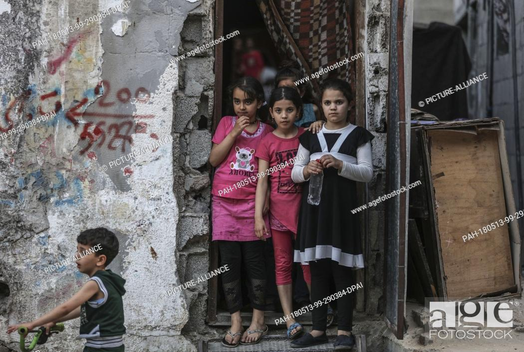 dpatop - Palestinian refugee girls stand at the doorway of a