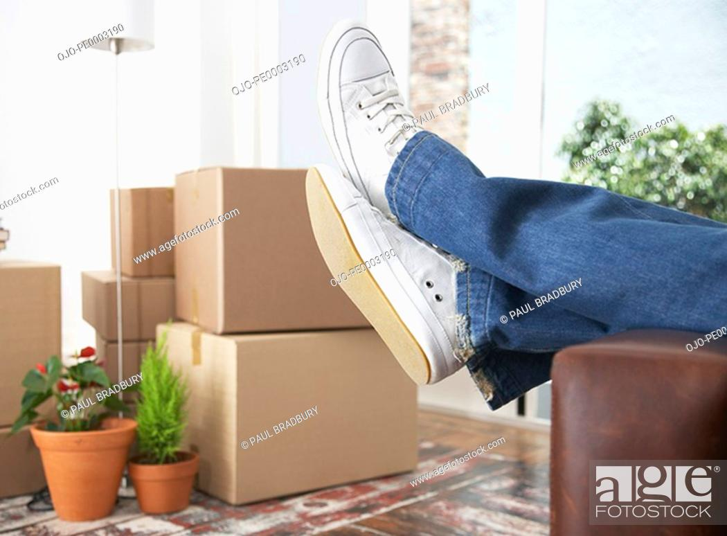 Stock Photo: Man lying down on sofa in home with cardboard boxes.