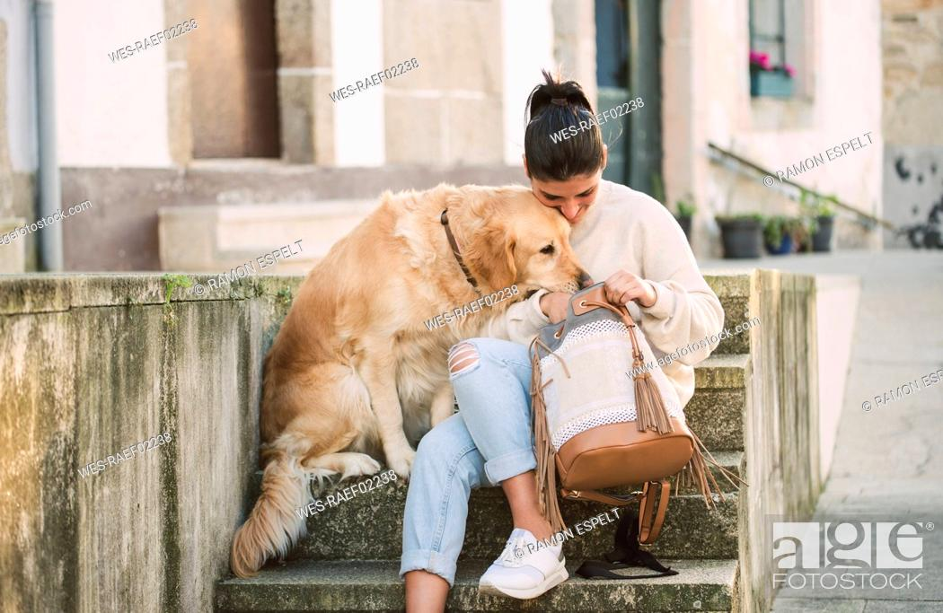 Stock Photo: Young woman with her Golden retriever dog on stairs looking in backpack.