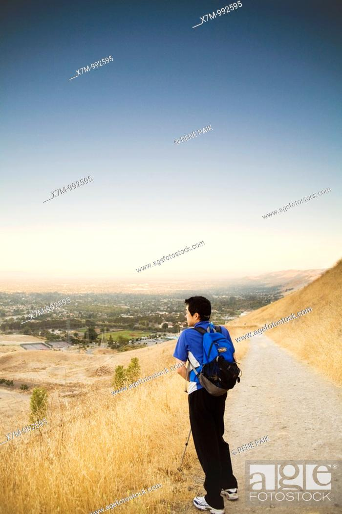 Stock Photo: Shortly after sunrise, a male Korean hiker looks down at the view of the city of Fremont and Ohlone College from the Peak Trail at Mission Peak Regional.