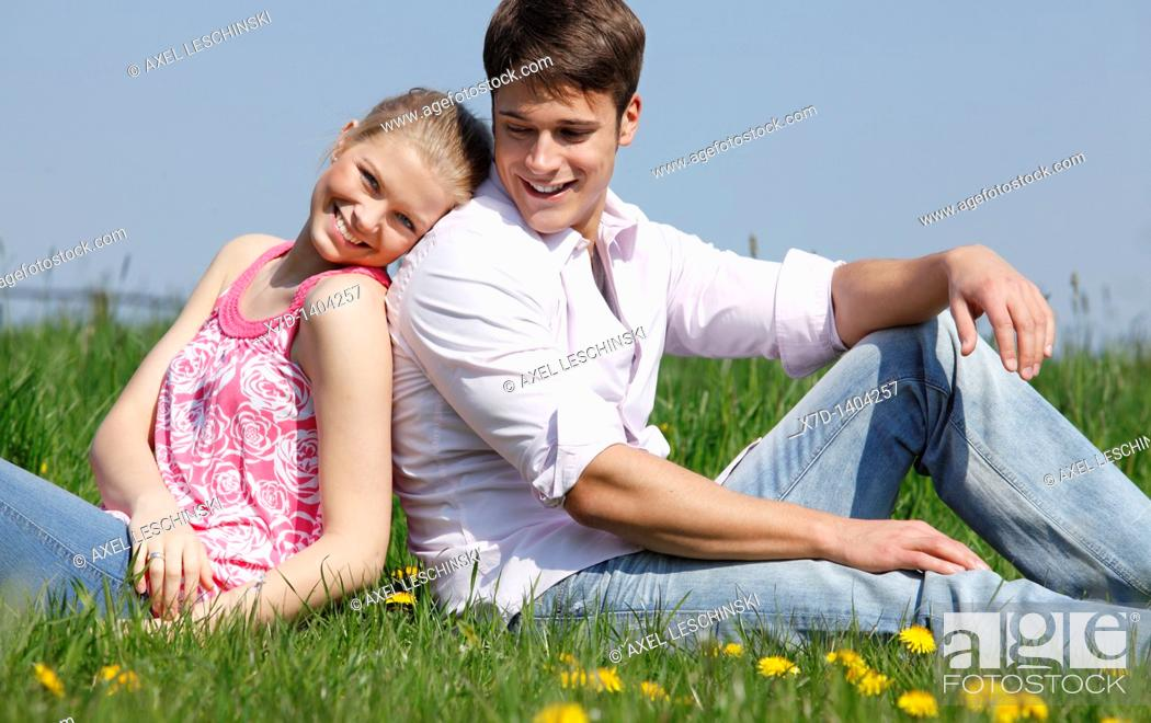 Stock Photo: couple sitting on meadow.
