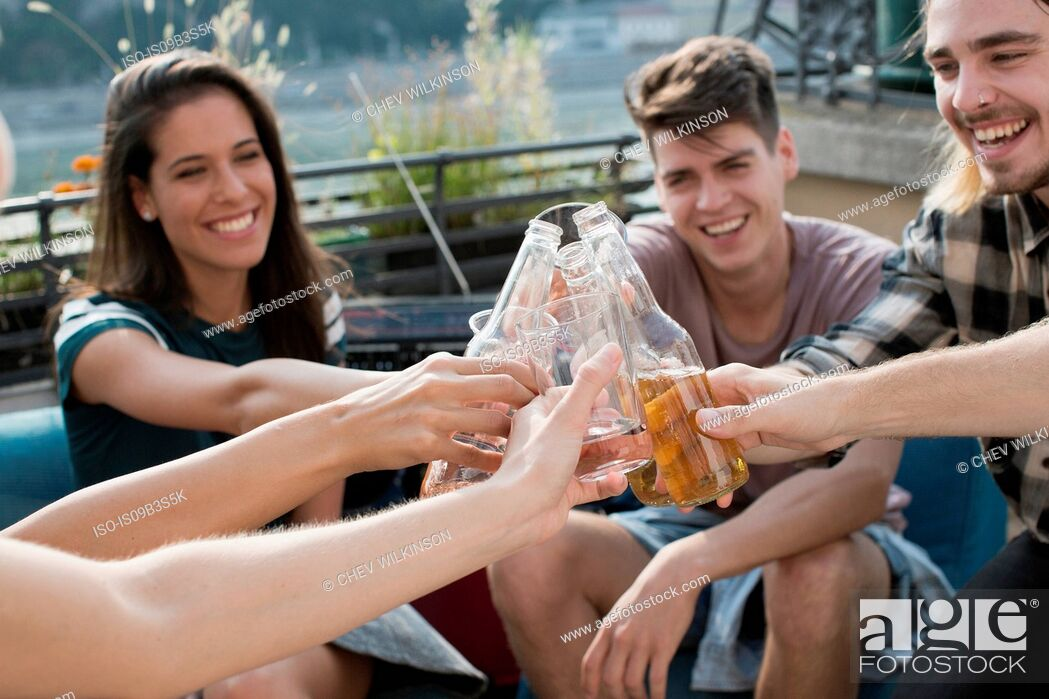 Stock Photo: Adult friends raising a toast at roof terrace party, Budapest, Hungary.