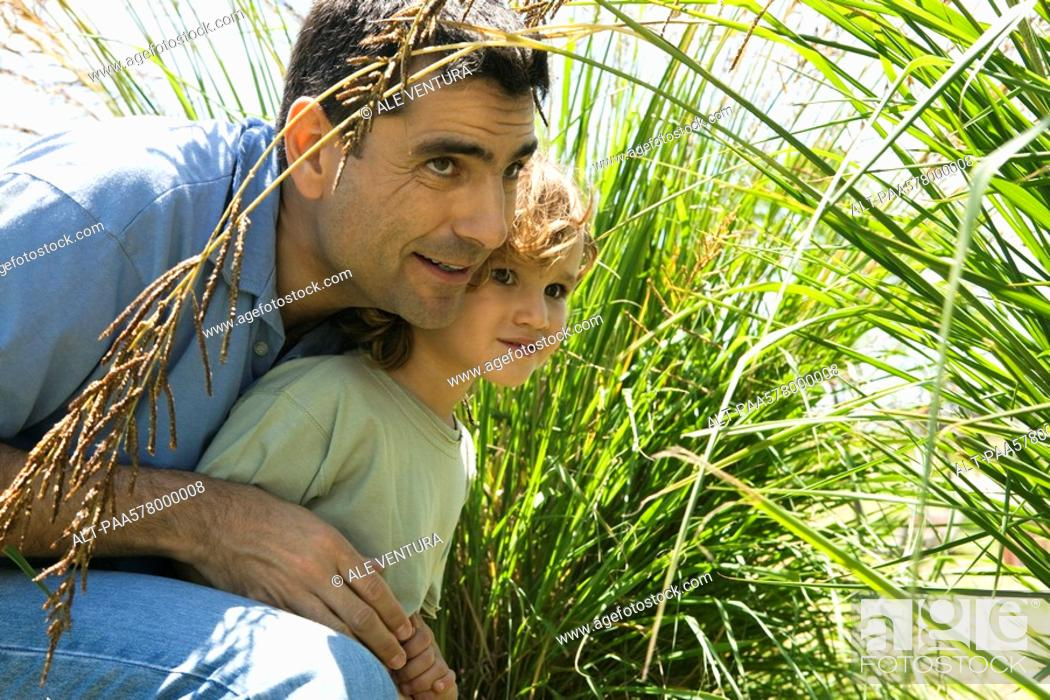 Stock Photo: Father and son hiding in tall grass.