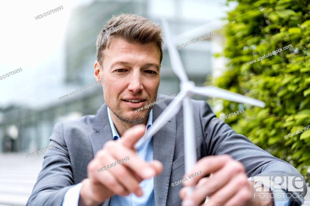 Stock Photo: Businessman with wind turbine model outdoors.