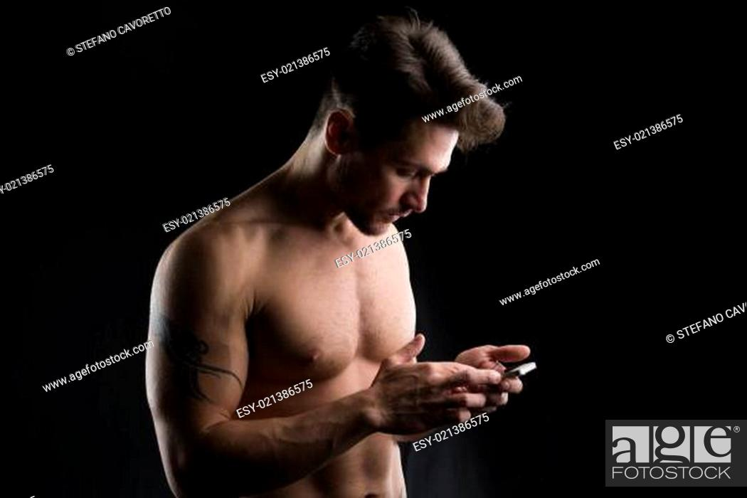 Stock Photo: Handsome shirtless muscular young man using cell phone.
