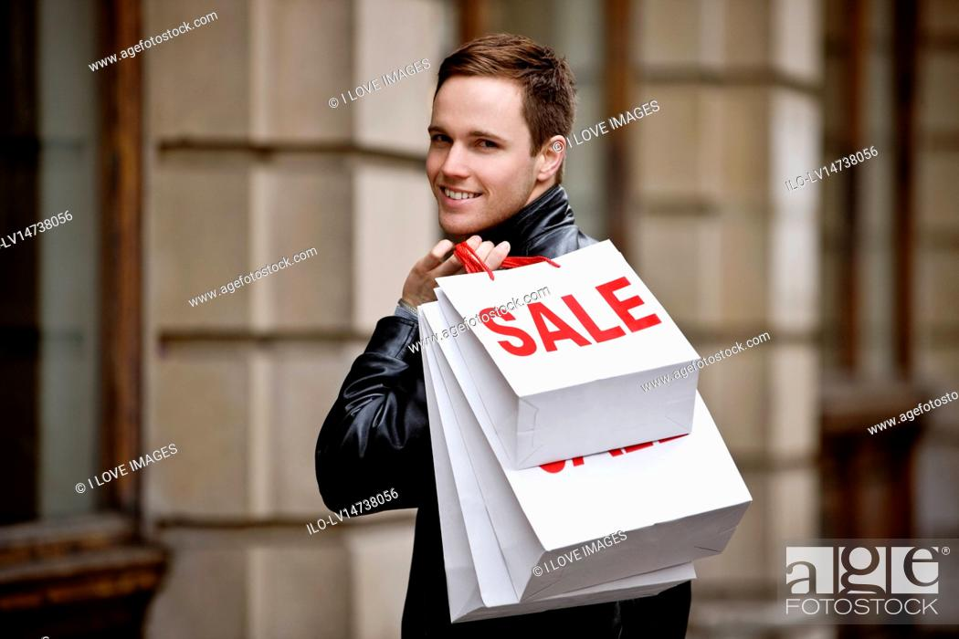 Stock Photo: A young man holding carrier bags.