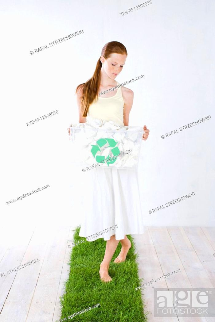 Stock Photo: woman carrying rubbish bin.