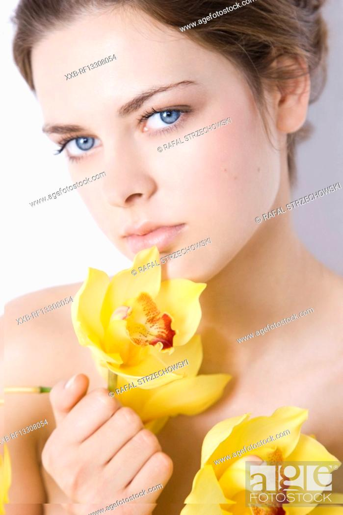 Stock Photo: nude woman with yellow orchid.