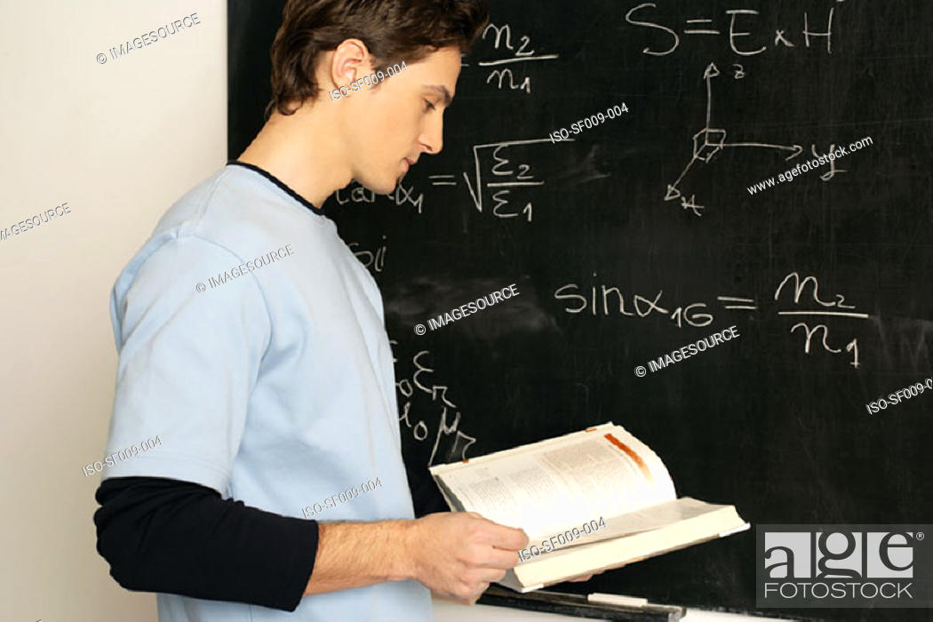Stock Photo: Young man standing in front of a blackboard.