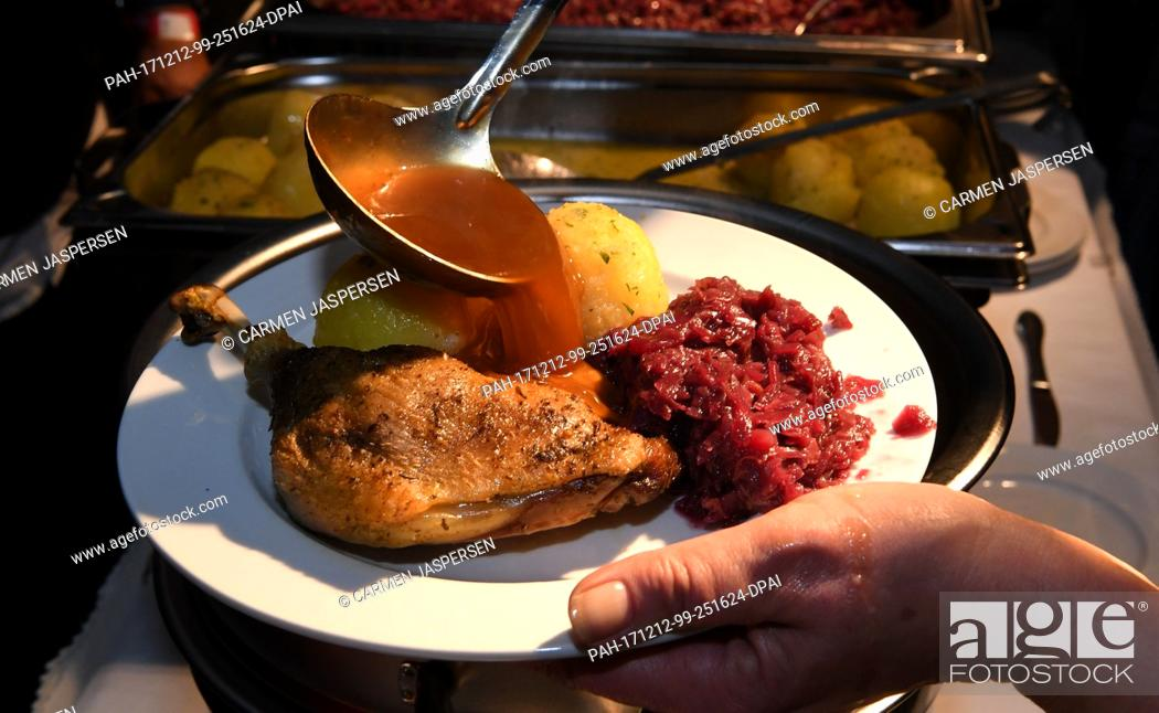 Stock Photo: Gravy is poured over duck legs with red cabbage and dumplings at the exhibition hall 4 during a charity meal in Bremen, Germany, 12 December 2017.
