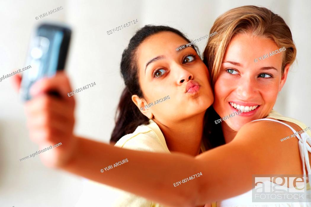 Stock Photo: Happy young girls making funny face while taking pictures of themselves through cellphone.