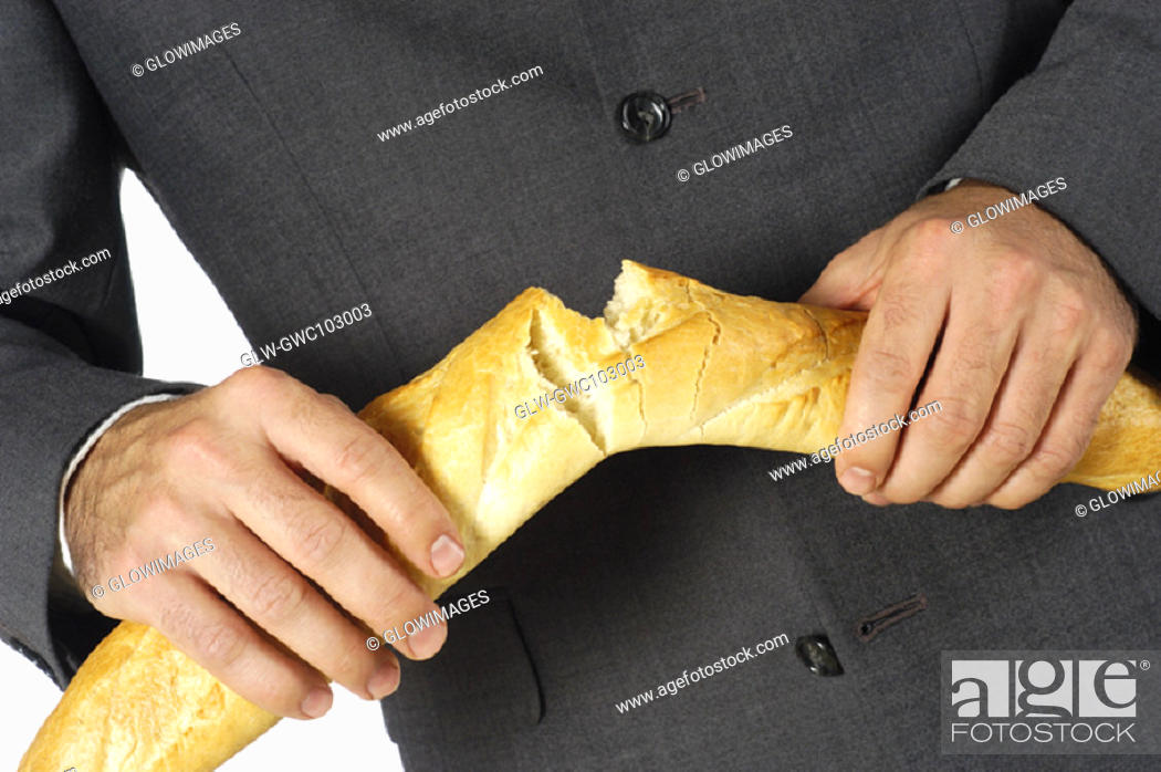 Stock Photo: Mid section view of a businessman breaking a loaf of bread.
