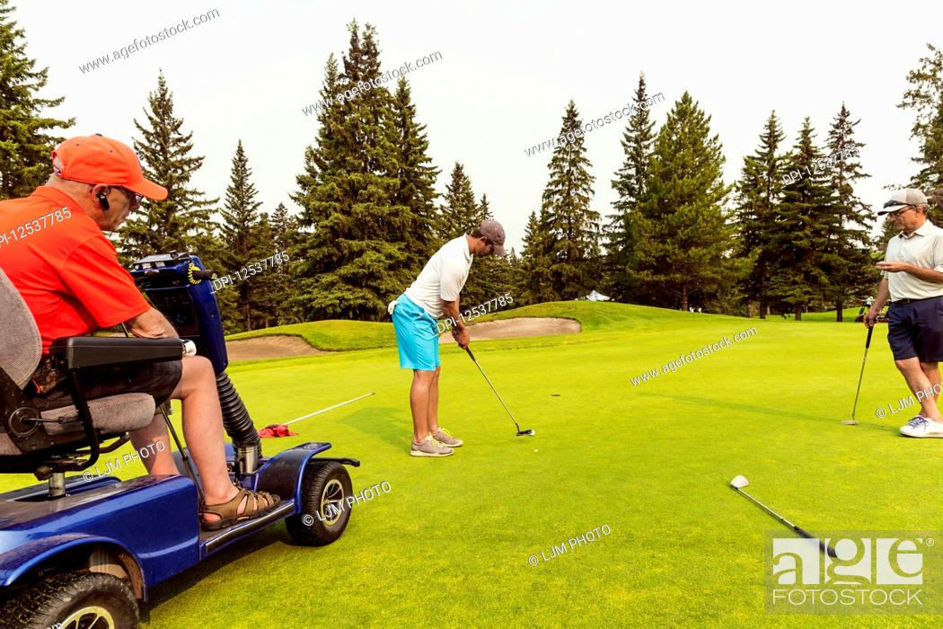 Stock Photo: Two able bodied golfers team up with a disabled golfer using a specialized powered golf wheelchair and putting together on a golf green playing best ball;.