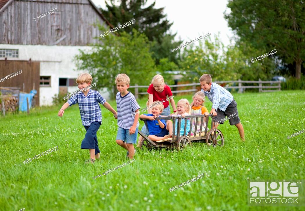 Stock Photo: Germany, Bavaria, Group of children playing with hand cart in front of farmhouse.
