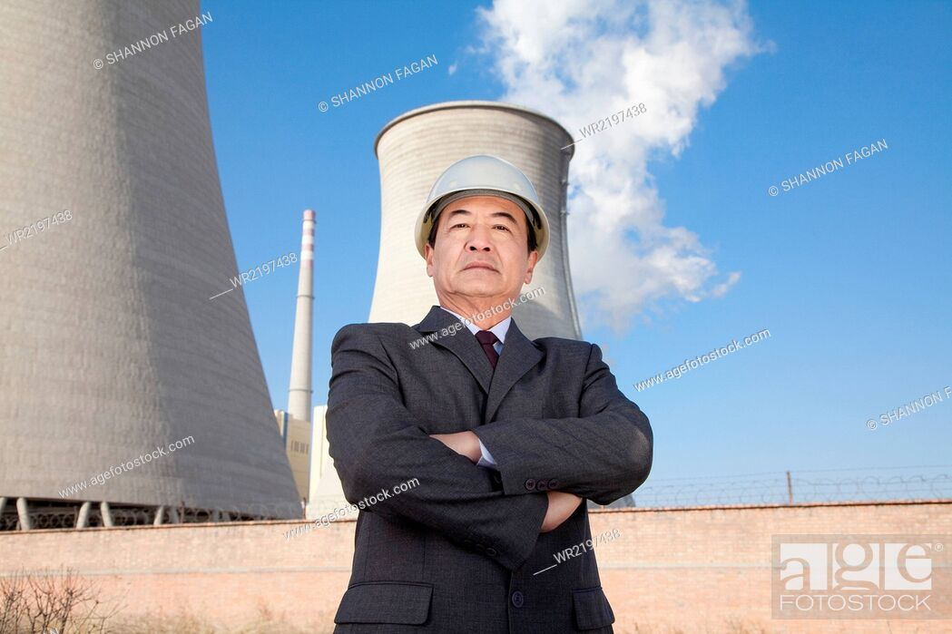 Stock Photo: Businessman in front of cooling tower.