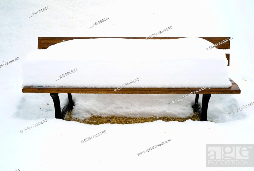 Stock Photo: Snow-covered bench in a public park.