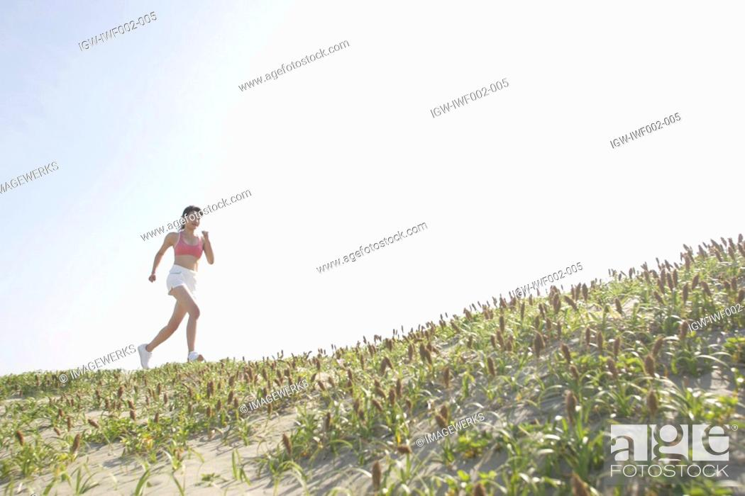 Stock Photo: Side view of a woman jogging during bright sunlight.