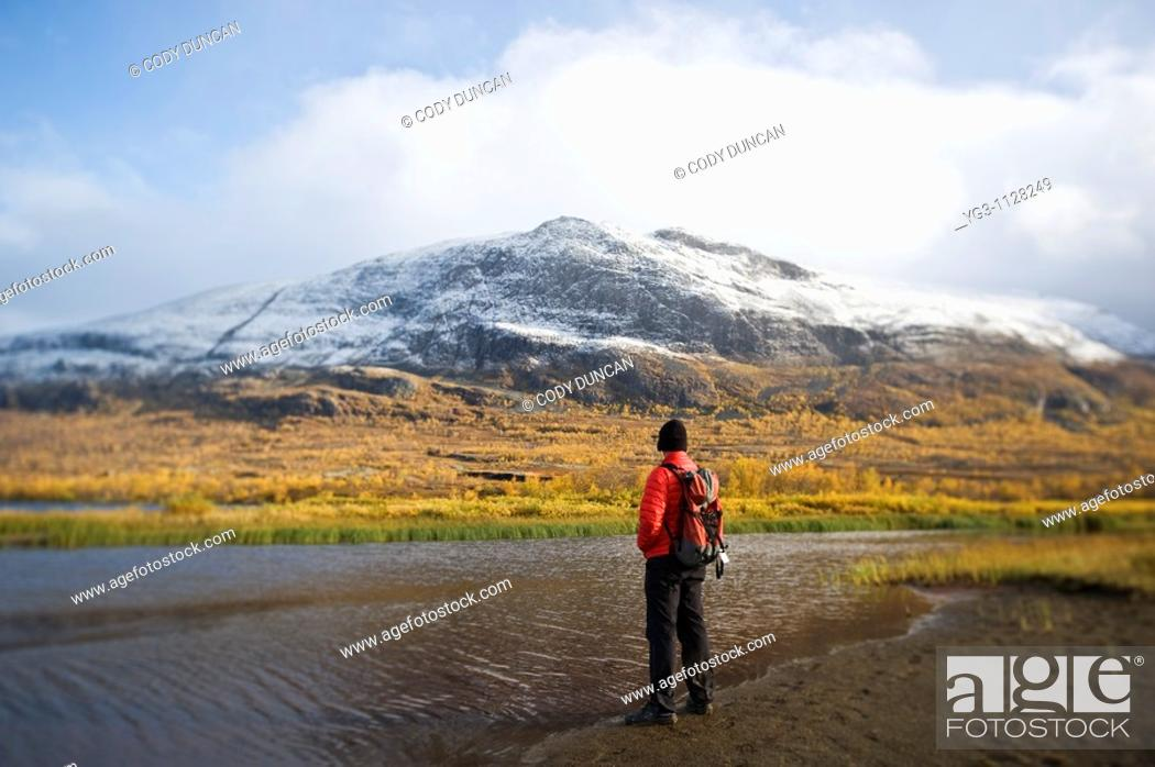 Stock Photo: Hiker stands on shore of Abeskojavri lake in autumn, Kungsleden trail, Lapland, Sweden.