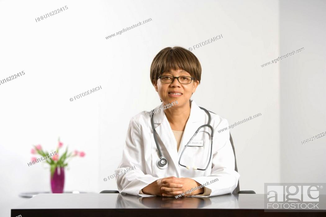 Stock Photo: African American middle-aged female doctor sitting at desk smiling and looking at viewer.