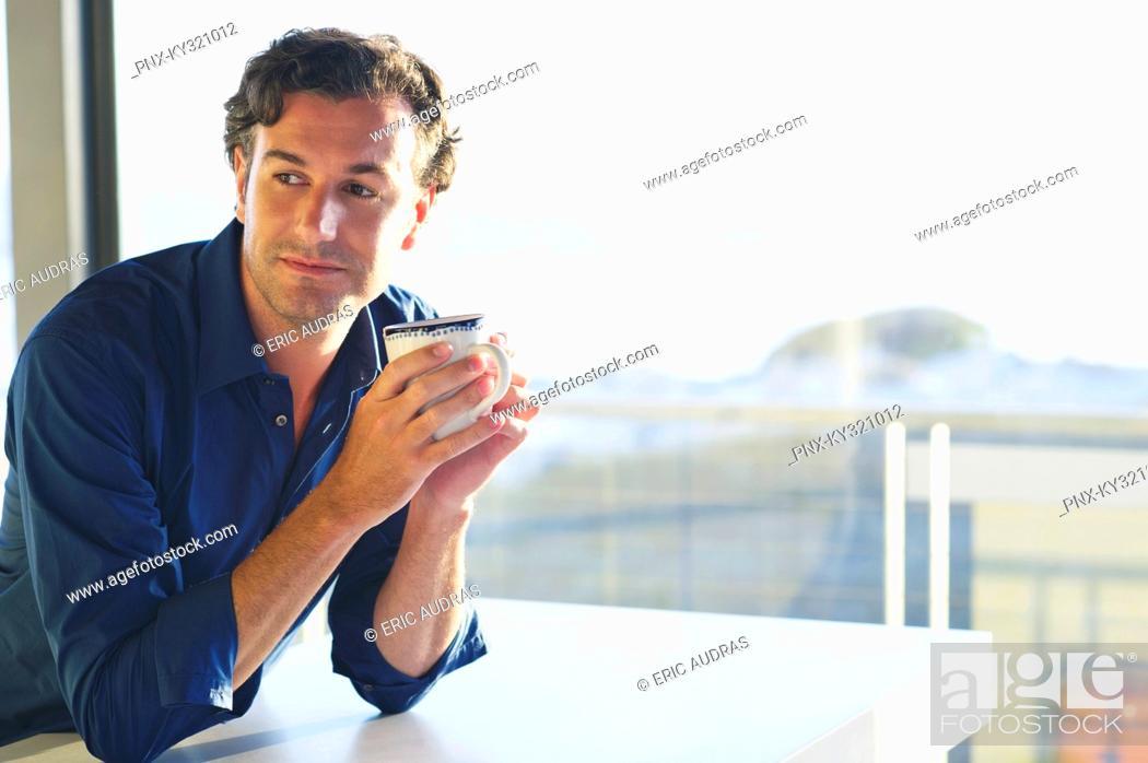 Stock Photo: Mid adult man drinking coffee.
