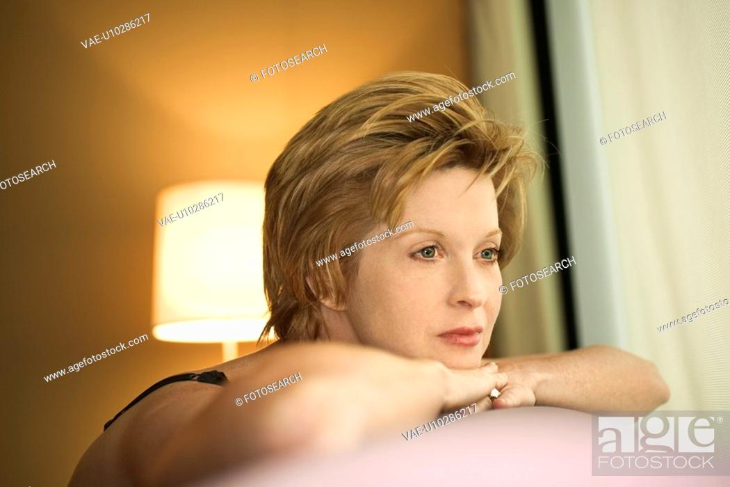 Stock Photo: Portrait of pretty Caucasian woman draped over sofa by window looking out.