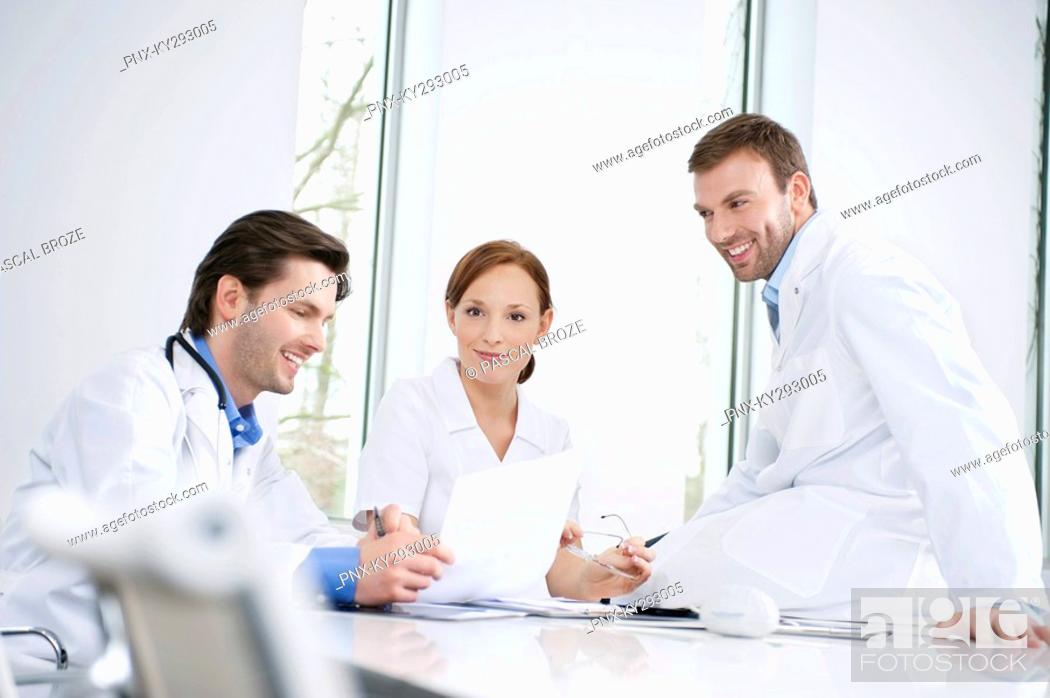 Stock Photo: Three doctors examining a medical report.