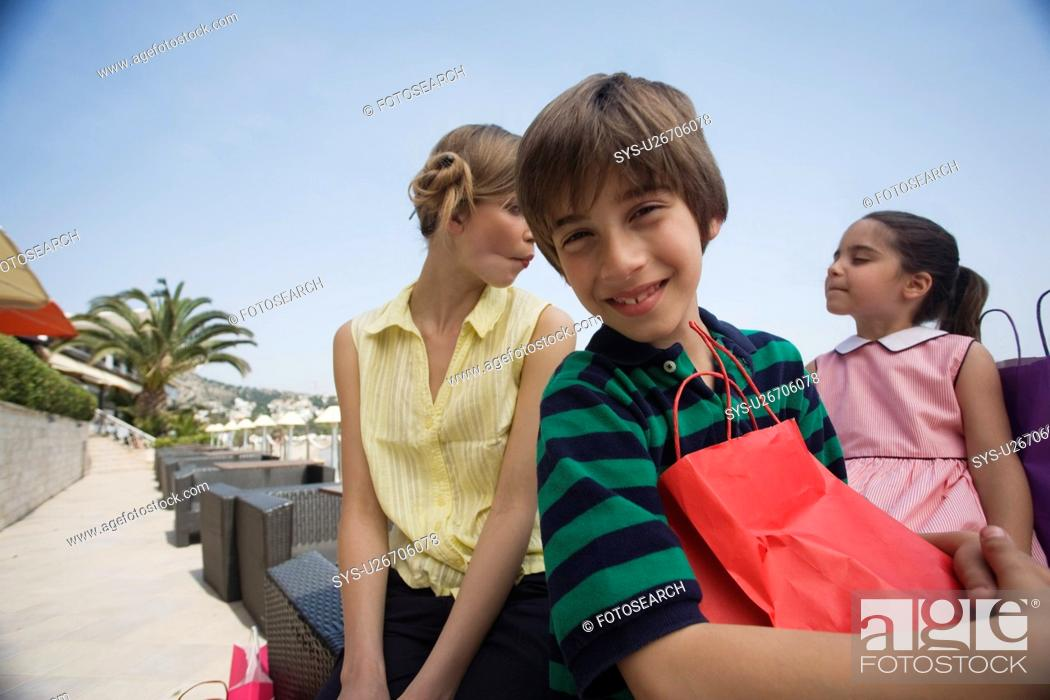 Stock Photo: Boy with shopping bag, mother and sister in background.