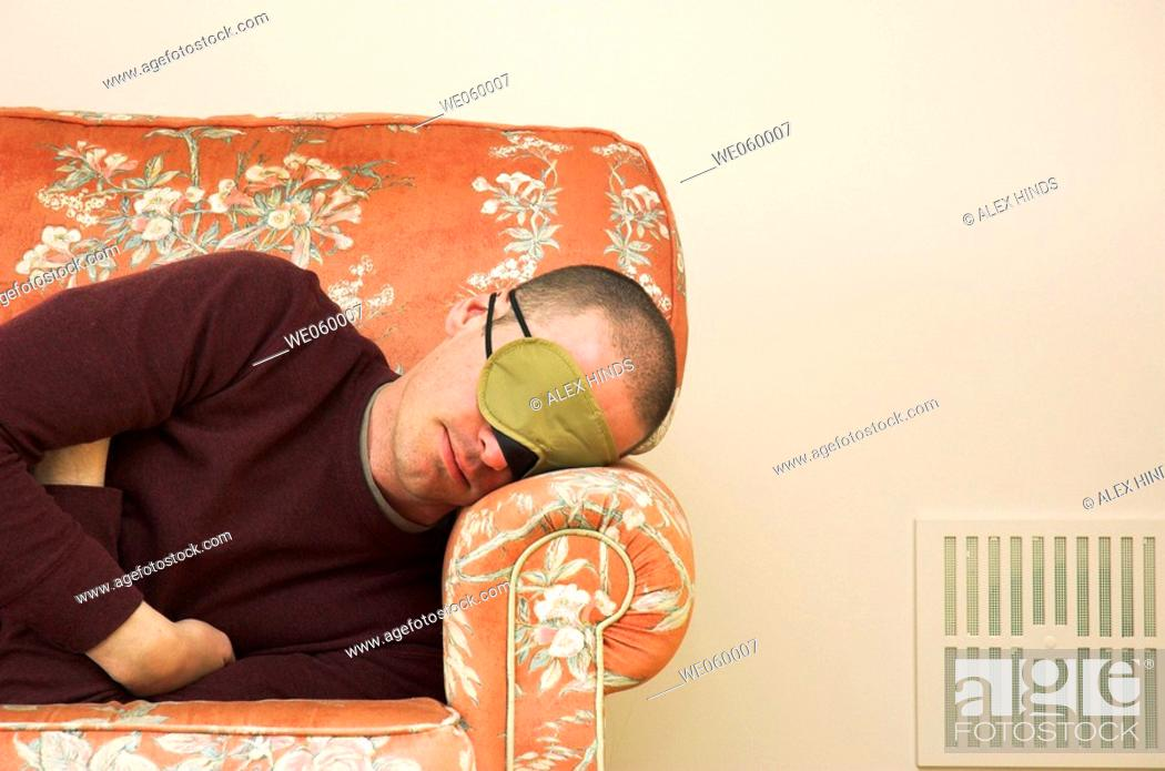 Stock Photo: Young man wearing eye mask catching up on some sleep on a floral sofa.