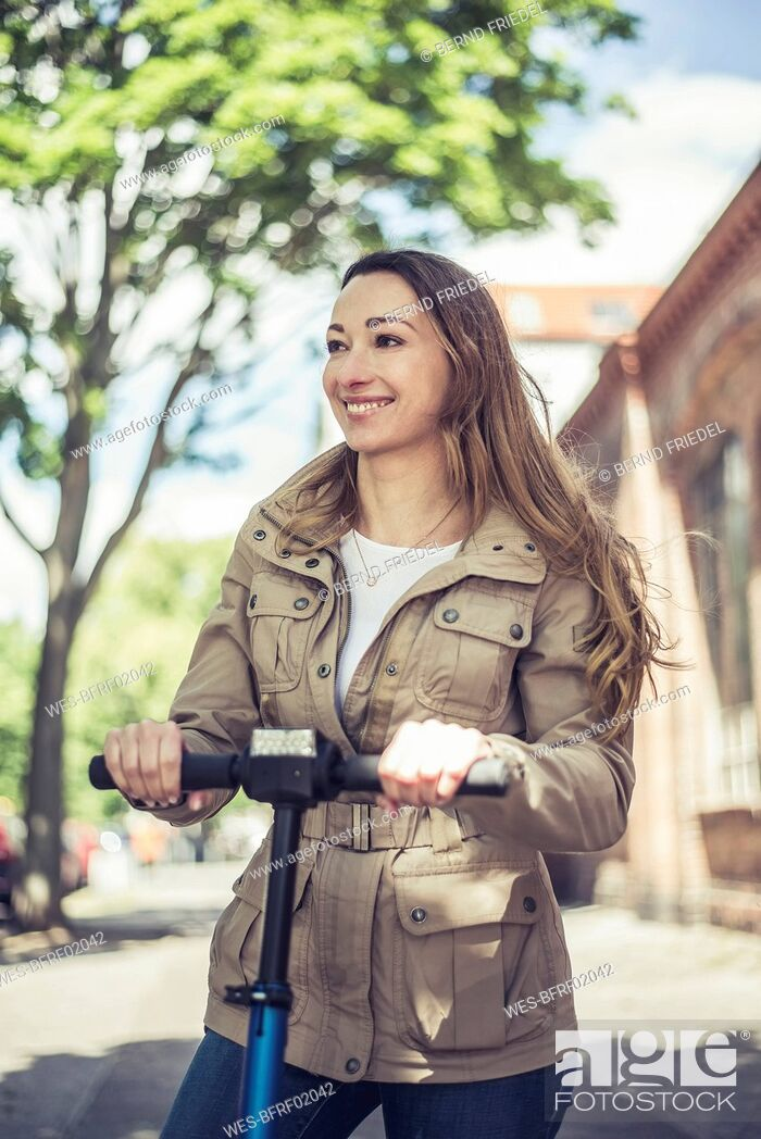 Stock Photo: Portrait of smiling woman with E-Scooter.