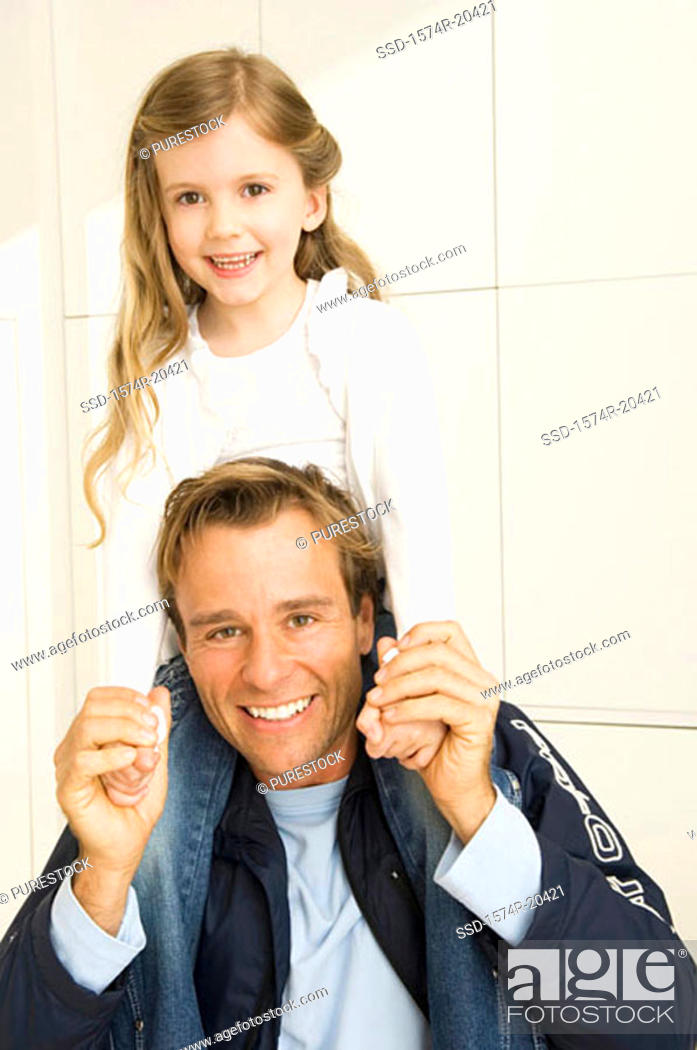 Stock Photo: Portrait of a young man carrying his daughter on his shoulders.