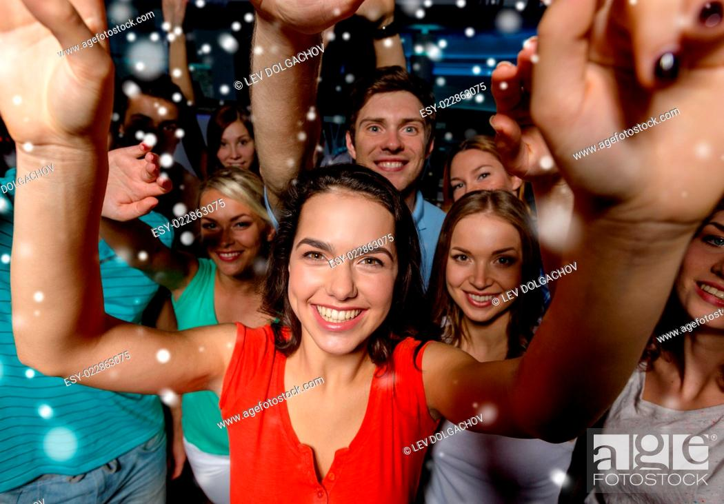 Stock Photo: party, holidays, celebration, friends and people concept - smiling friends dancing and waving hands in club and snow effect.