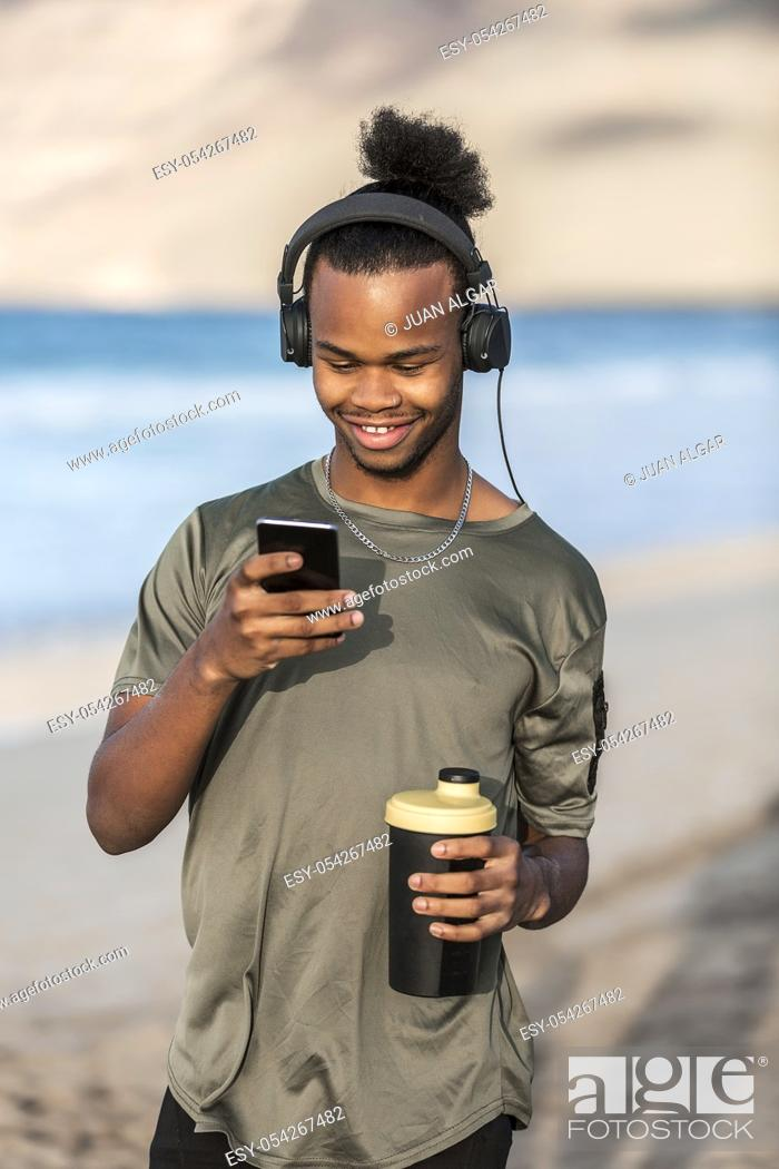 Stock Photo: Cheerful African American guy holding cup of hot drink and listening to music while standing near sea and using smartphone.
