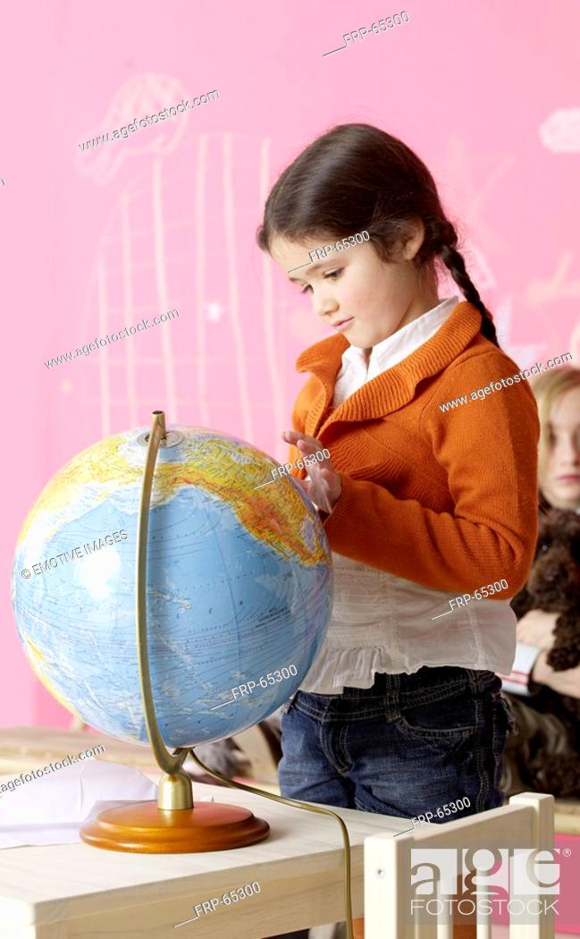 Stock Photo: Girl standing next to a globe.