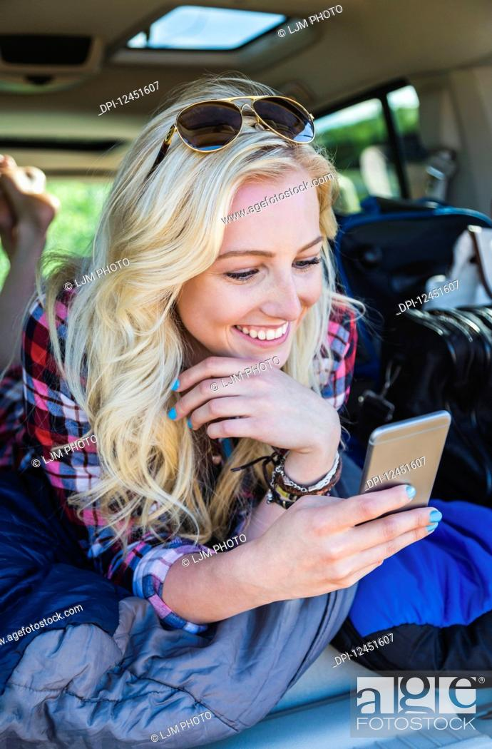 Stock Photo: A young woman on a road trip lays in the back of a vehicle with a sleeping bag using her smart phone; Edmonton, Alberta, Canada.
