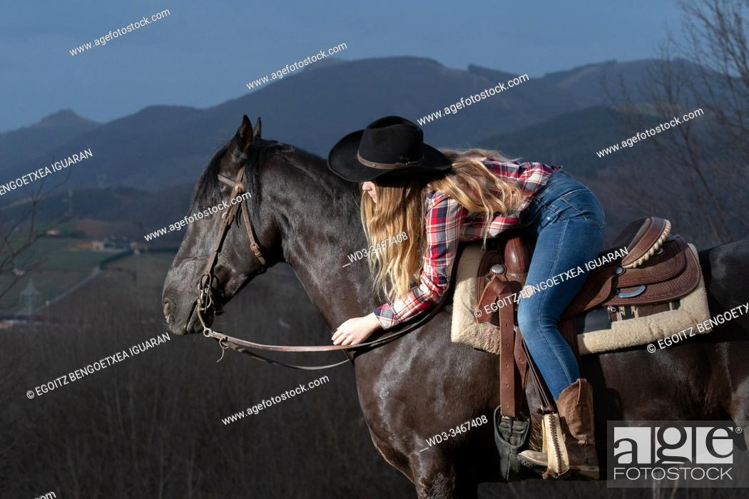 Imagen: A blonde teenager girl hugging and lying on her black horse.