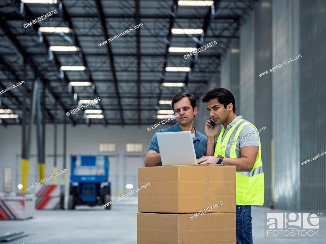 Stock Photo: Workers using laptop and cell phone in warehouse.