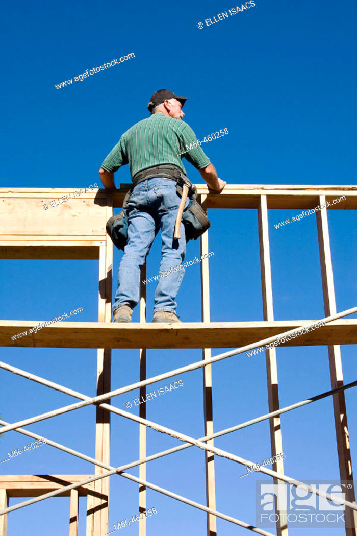Stock Photo: Carpenter standing on scaffolding looking over the top of second story wall at a construction site.