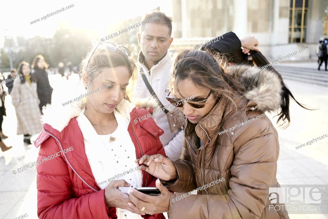Stock Photo: friends using smartphone.