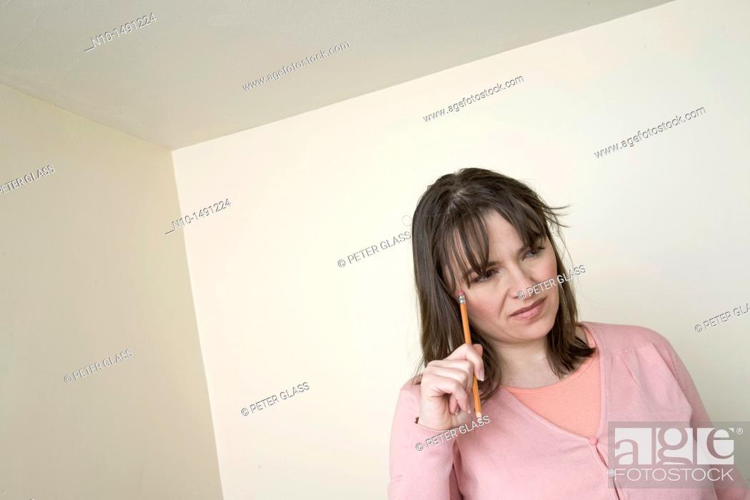 Stock Photo: Young woman holding a pencil.