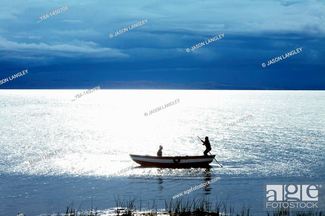 Stock Photo: Two boys in a small boat on Lake Titicaca, silhouetted by the setting sun with dark storm clouds in the distance  Llachon, Capachica Peninsula, near Puno, Peru.