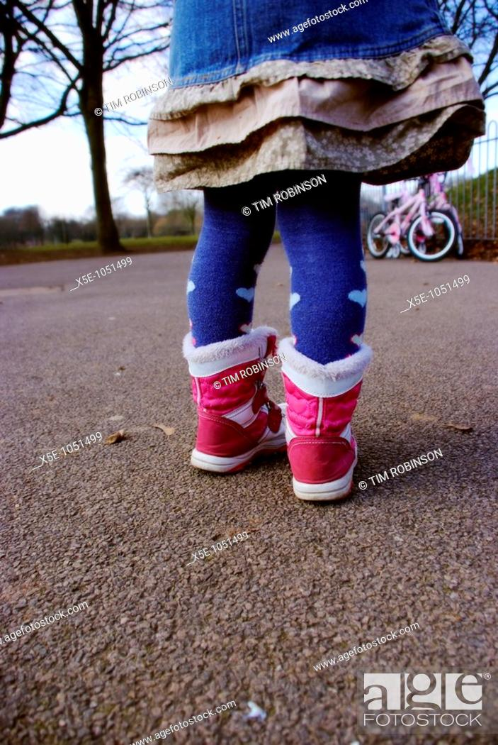 Stock Photo: Rearview legs and feet of 6 year girl wearing red boots in playground.