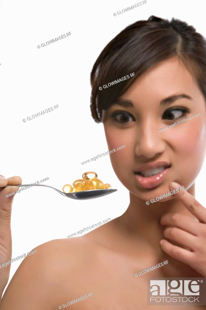 Stock Photo: Close-up of a young woman holding a spoon of pills.