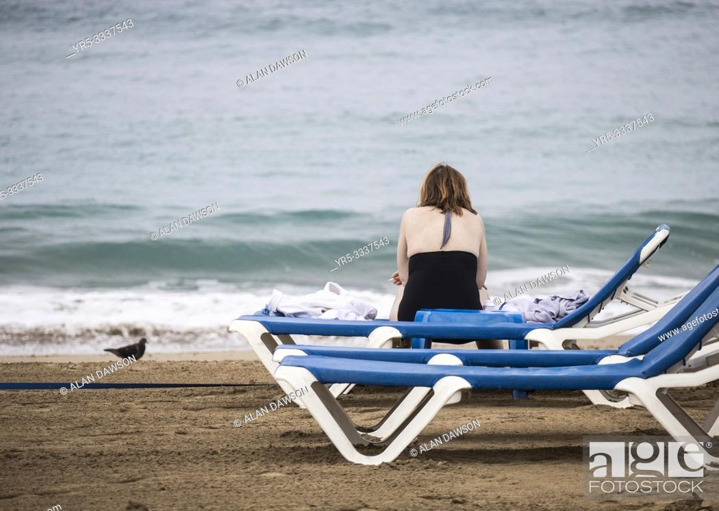 Stock Photo: Rear view of woman alone on beach sitting on sunbed with cigarette in hand. Gran Canaria, Canary Islands, Spain.
