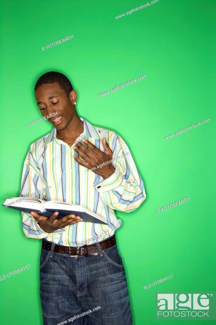 Stock Photo: Portrait of African-American teen boy reading book standing in front of green background.