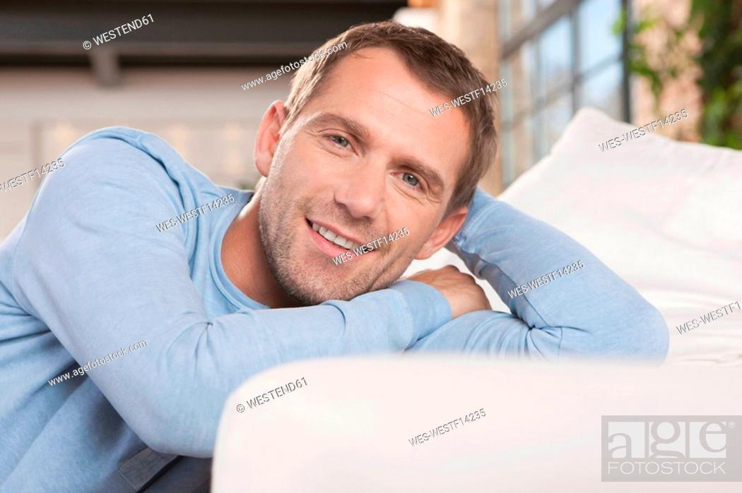 Stock Photo: Germany, Cologne, Man sitting by sofa, smiling, portrait.